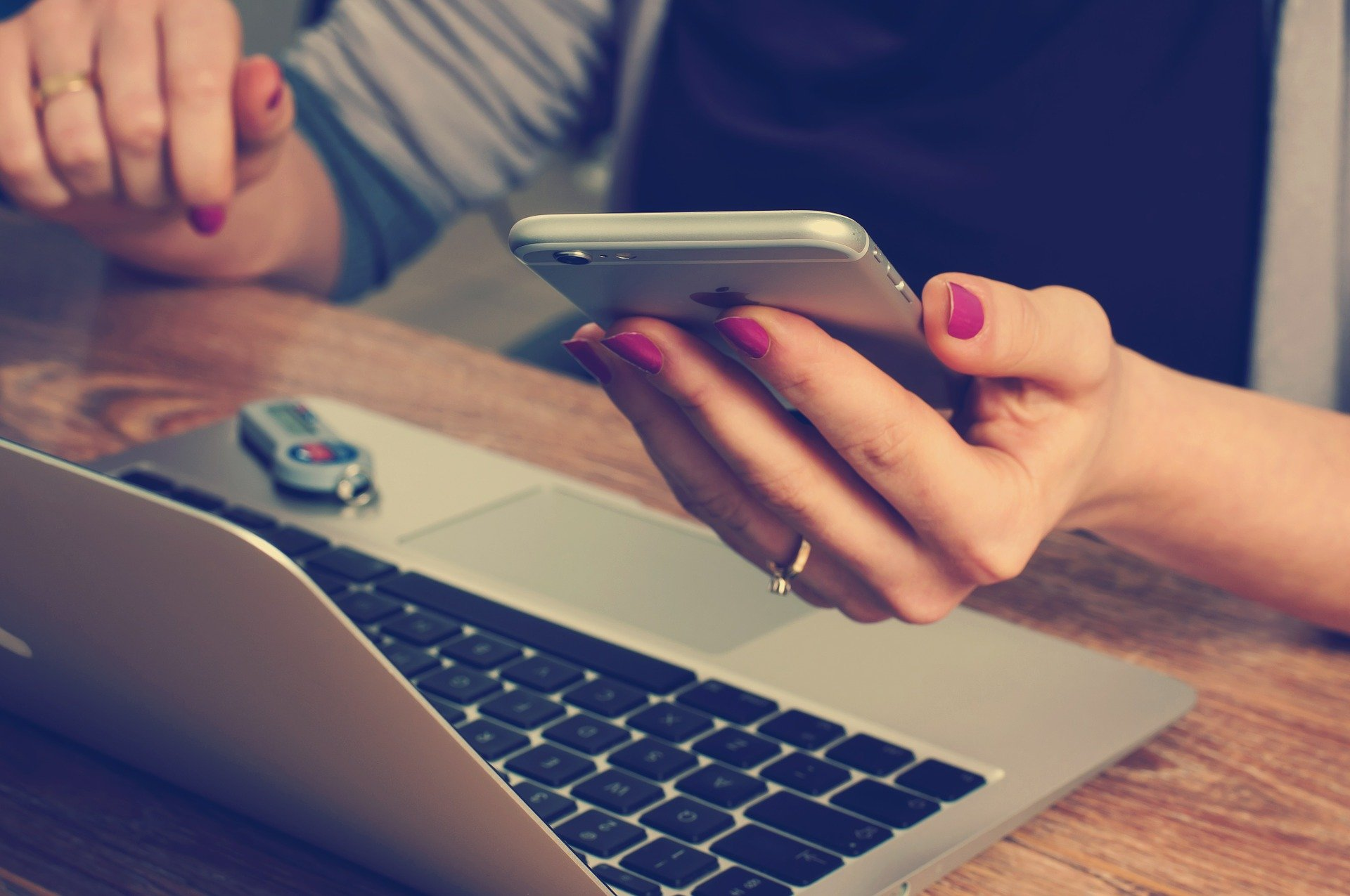 Tietokone ja ihminen, jolla puhelin kädessä.