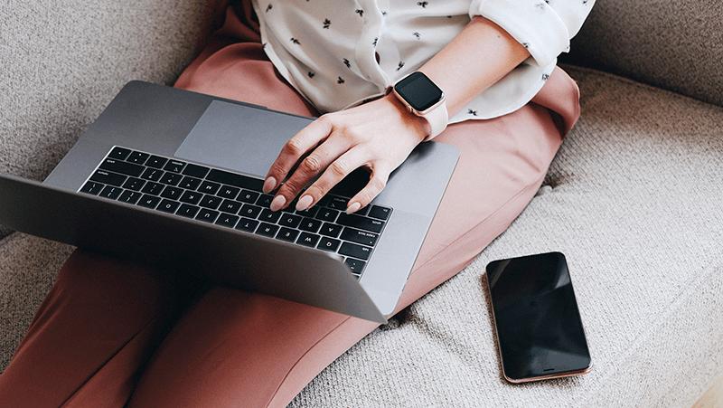Nainen istuu sohvalla kannettava tietokone sylissä